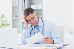 Tensed male doctor reading document in clinic Royalty Free Stock Images