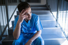 Tensed male nurse sitting on staircase Royalty Free Stock Image
