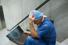 Tensed male surgeon examine x-ray on staircase. In hospital Royalty Free Stock Photography