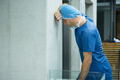 Tensed male surgeon leaning on wall near elevator. In hospital Stock Images