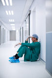 Tensed male surgeon sitting in corridor. Of hospital Royalty Free Stock Images