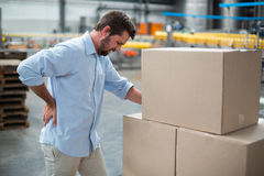 Tensed male worker standing with back pain. In factory royalty free stock photos