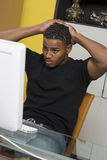 Tensed Man Looking At Computer Screen. Tensed young African American men looking at computer screen Royalty Free Stock Photo