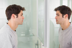 Tensed man looking at self in bathroom mirror Stock Photos