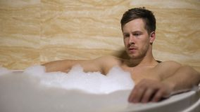 Tensed man taking bath, thinking about work and cant relax, difficult decision. Stock footage stock video
