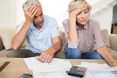 Tensed mature couple with bills and calculator at home Royalty Free Stock Photos