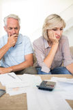 Tensed mature couple with bills and calculator at home Stock Image