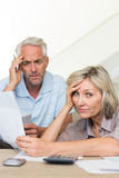 Tensed mature couple with bills at home Royalty Free Stock Photography