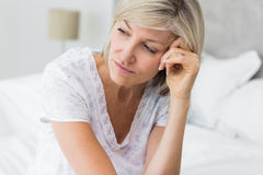 Tensed mature woman sitting in bed Royalty Free Stock Photography