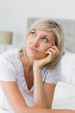 Tensed mature woman sitting in bed Stock Image