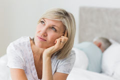 Tensed mature woman sitting in bed with man in background Stock Photo