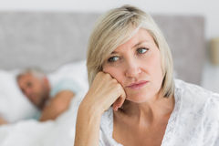 Tensed mature woman sitting in bed with man in background Royalty Free Stock Photos