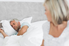 Tensed mature woman sitting in bed with man in background Stock Photography