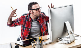 Tensed middle aged casual man working with stress and exasperation. Raising angry hands in front of his computer, white background, contrast effects Stock Photography