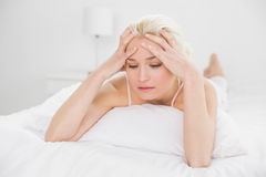 Tensed pretty woman lying in bed Royalty Free Stock Images