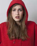 Tensed 20s girl protecting herself in hoodie expressing fear or disagreement. Disappointment concept - unhappy young woman with long brown hair out of red hoodie Royalty Free Stock Image