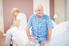 Tensed senior couple sitting on bed. At home Royalty Free Stock Photos