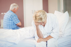Tensed senior couple sitting in bedroom Royalty Free Stock Images