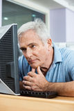 Tensed Senior Man Looking At Computer In Class. Tensed senior man looking at computer monitor while sitting in class Royalty Free Stock Image