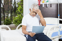 Tensed Senior Man Reading Reports In Rehab Center Stock Photography