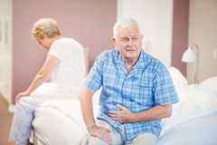 Tensed senior man and woman sitting on bed Stock Photography