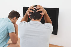 Tensed soccer fans watching tv Royalty Free Stock Images
