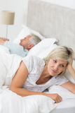 Tensed woman lying besides man in bed Royalty Free Stock Photos
