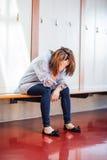 Tensed woman sitting in locker room Royalty Free Stock Photos