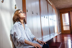 Tensed woman sitting in locker room Stock Images