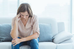 Tensed woman sitting on sofa Stock Image