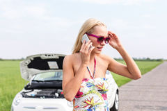 Tensed woman using cell phone on country road with broken down car in background Royalty Free Stock Images