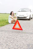 Tensed woman using cell phone while sitting by broken down car Royalty Free Stock Image