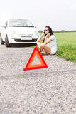 Tensed woman using cell phone while sitting by broken down car Stock Photo
