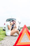 Tensed woman using cell phone while sitting on country road by broken down car Stock Photo