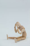 Tensed wooden figurine sitting with hands on head Stock Photo