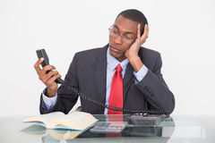 Tensed young Afro businessman looking at telephone receiver Stock Photos