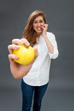Tensed young beautiful woman grinding her teeth holding an apple Royalty Free Stock Photography