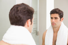 Tensed young man looking at self in bathroom mirror Stock Photos