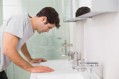 Tensed young man at washbasin in bathroom Royalty Free Stock Photos