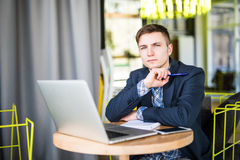 Tensed young man working on laptop at cafe table and thinking stock image