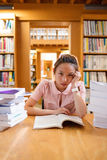 Tensed young woman studying in library Stock Images