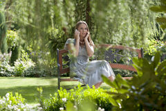 Tensed young woman using cell phone on bench in park Stock Images