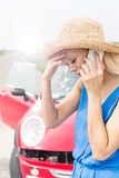 Tensed young woman using cell phone by broken down car Stock Images