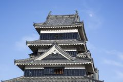 Samurai Matsumoto Tenshu. A Tenshu is the highest tower of a Japanese castle or temple. Under a blue sky, with scant clouds and an almost full moon, this is the Stock Photos