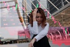 Tensión asiática joven subrayada de la sensación de la empresaria con el comercio contra mercado de acción y gráfico de la palmat Foto de archivo