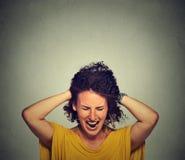 tensión La mujer tensionada va loca tirando de su pelo en la frustración foto de archivo
