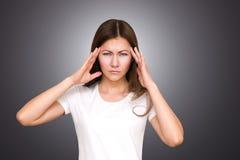 Tensión y dolor de cabeza Mujer joven que tiene dolor de la jaqueca Fotografía de archivo