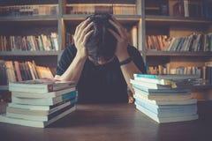 Tensión y hombre cansado bajo presión mental mientras que libro de lectura que prepara el examen en biblioteca imagen de archivo libre de regalías