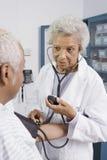 Tension artérielle de docteur Measuring Patient Images libres de droits