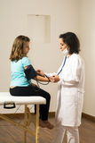 Tension artérielle de docteur Taking Girl's. Vertical Photographie stock